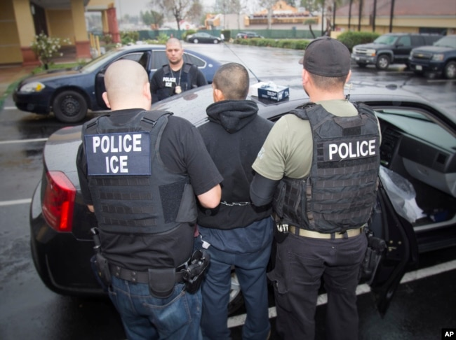 FILE - A photo released by U.S. Immigration and Customs Enforcement shows foreign nationals being arrested, Feb. 7, 2017, during a targeted enforcement operation conducted by U.S. Immigration and Customs Enforcement (ICE).