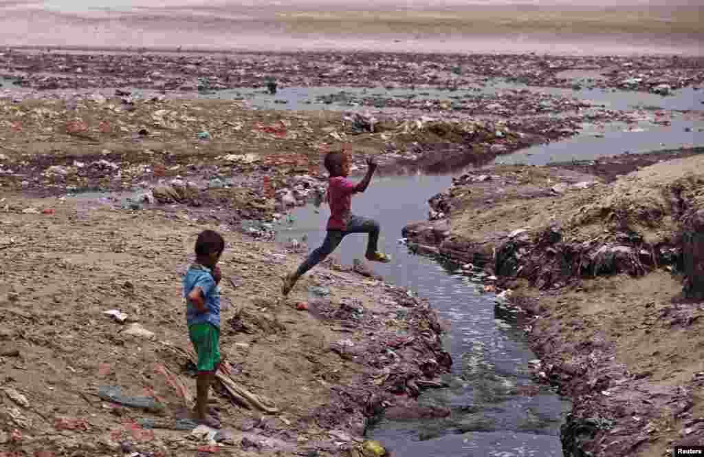 인도 동북부 칸푸르의 갠지스강으로 유입된 가죽 무두질 공장의 오염된 물이 배수지에 고여 있다. 소년이 그 위를 힘차게 뛰고 있다.