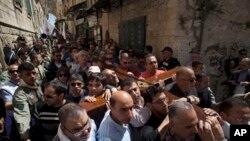 Hrišćanski hodočasnici nose krst prema Crkvi svetog Groba u Jerusalimu.