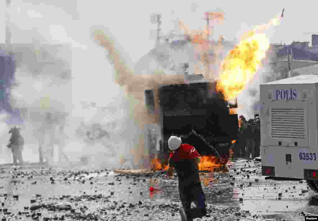 A protester throws a petrol bomb towards a crowd control vehicle in Taksim Square in Istanbul, June 11, 2013.