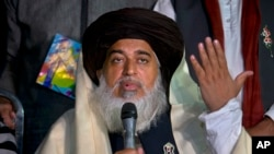 FILE - Khadim Hussain Rizvi, founder of Tehreek-e-Labbaik Pakistan, gestures during a news conference in Islamabad, Pakistan, Nov. 26, 2017.