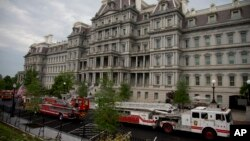 Pemadam kebakaran parkir antara gedung The Eisenhower Executive Office Building dan Sayap Barat Gedung Putih setelah ada panggilan kebakaran (11/5). (AP/Carolyn Kaster)