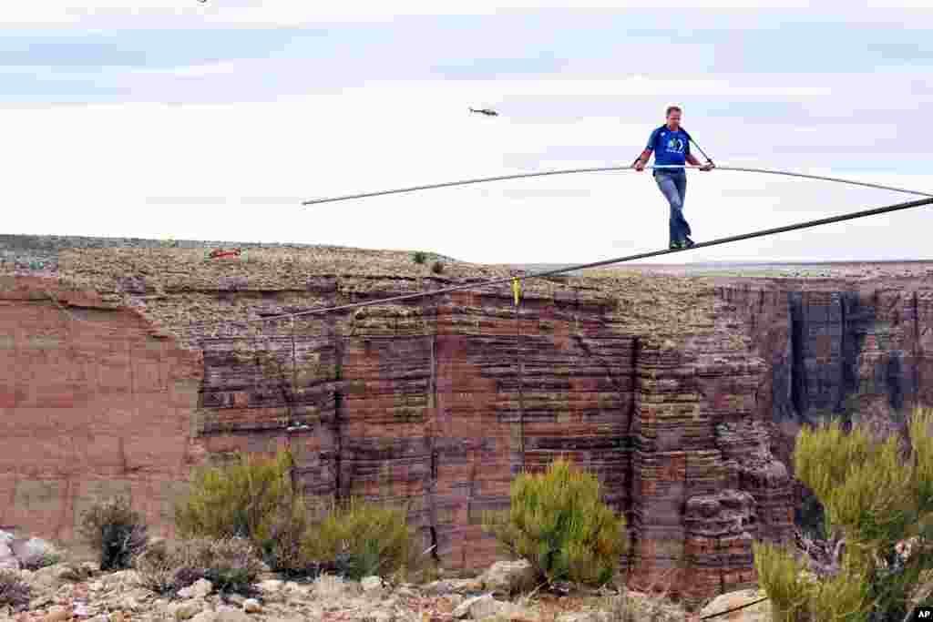 Tay mạo hiểm Nik Wallenda gần hoàn tất nỗ lực đi trên dây căng qua hẻm núi sông Little Colorado ở đông bắc bang Arizona, ngày 23 tháng 6, 2013. Anh phải vượt qua hẻm núi trên sợi dây cáp bằng thép chỉ rộng 5cm.