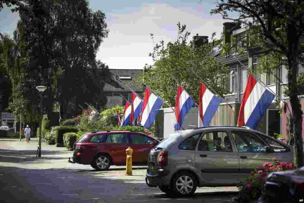 Bendera-bendera Belanda dipasang setengah tiang untuk menghormati para korban jatuhnya pesawat Malaysia Airlines MH17, di Delft, Belanda (23/7). (AP/Phil Nijhuis)