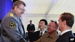 图为梅德韦杰夫(右)8月24日微笑着观看金正日与国防部的维克多·叶利谢耶夫握手