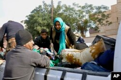 Iraqi security forces and allied Sunni tribal fighters help trapped civilians get to safer areas in Ramadi, 70 miles (115 kilometers) west of Baghdad, Iraq, on Jan. 2, 2016, after multiple IS suicide bombings.