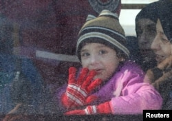 A child reacts from inside a bus evacuating people from a rebel-held sector of eastern Aleppo, Syria Dec. 15, 2016.