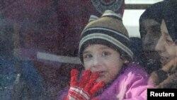 مشرقی حلب سے جانے کے لیے بس میں سوار بچے کے چہرے پر خوشی نمایاں ہے۔ 15 دسمبر 2016