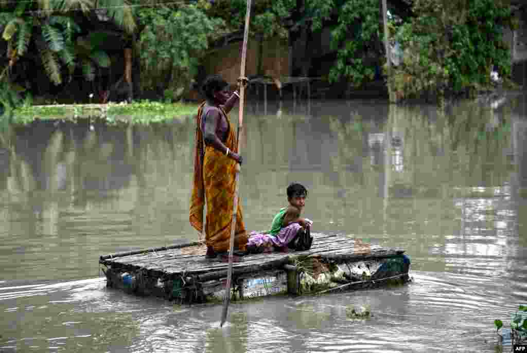A woman paddles on a tinkered boat as a child looks on at the flood-affected Kayakuchi village in Barpeta district of the Assam state, India.