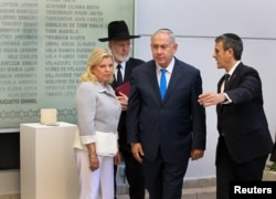 Israeli Prime Minister Benjamin Netanyahu, from left, and his wife Sara, alongside Agustin Zba, President of the Argentine Israeli Mutual Association Jewish community center, walk past a wall with names of the victims of the 1994 AMIA bombing in Buenos Aires.