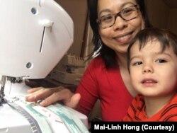 Mai-Linh Hong và con trai 4 tuổi bên chiếc máy may mà cô dùng để may khẩu trang cho nhóm Auntie Sewing Squad. (Photo courtesy of Mai-Linh Hong)