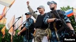 FILE - Self-styled governor of Luhansk region Valery Bolotov (C) delivers a speech during a rally to mark and celebrate the announcement of the results of the referendum on the status of Luhansk region in Luhansk, May 12, 2014.