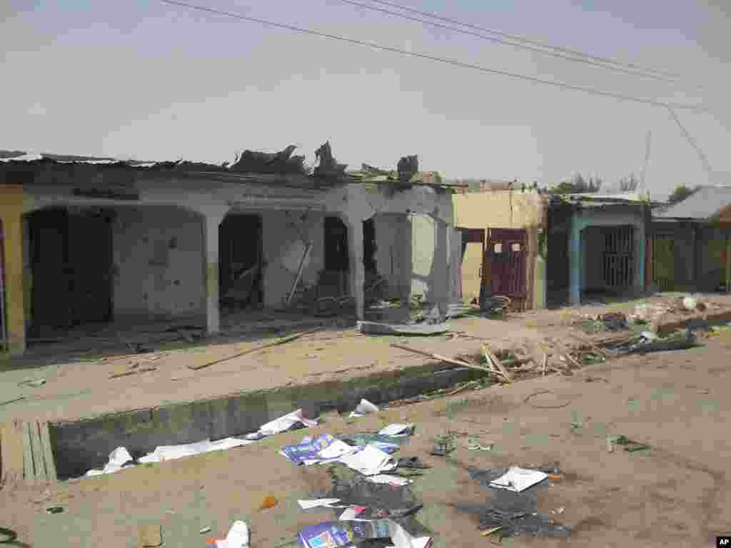 Damaged buildings and bloodstains on the street can be seen following a suicide bomb explosion at a World Cup viewing center, Damaturu, Nigeria, June 18, 2014.