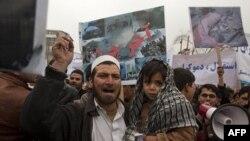 Một người đàn ông Afghanistan và con trai tham gia cuộc biểu tình tại Kabul, 6/3/2010