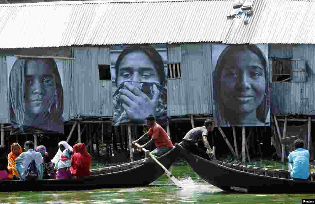 """Boats carrying slum dwellers pass photographs of garment workers taken by students of the Counter Foto photography department, by the waterfront of Korail slum at Gulshan area in Dhaka September 13, 2013. The photographs of garment workers are a celebration of the hardworking Bengali woman, in support of their struggle for socio-economic justice, and are part of the """"Dignity in Industry"""" project by French artist J.R. and Inside Out Project, organizers said."""