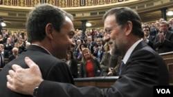 El presidente saliente y el electo, José Luis Rodríguez Zapatero y Mariano Rajoy se saludan al acabar la sesión de investidura.