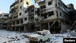 Sebuah mobil yang rusak dan bangunan yang tertutup salju terlihat di daerah Jouret al Shayah, Homs, Suriah, 10 Januari 2013. (Foto: dok). Para aktivis melaporkan pasukan yang setia kepada Presiden Assad telah menewaskan lebih dari 100 orang di Homs, Suriah Tengah.