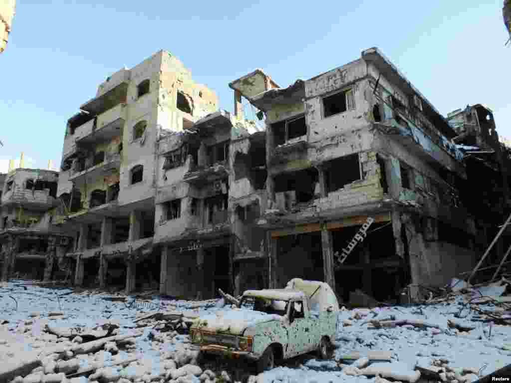 A damaged car and buildings covered with snow are seen in the Jouret al Shayah area of Homs, Syria, January 10, 2013.