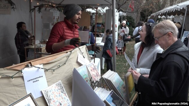 Artist Carlos Carmonamedina talks to customers while selling his postcards in Washington, D.C.