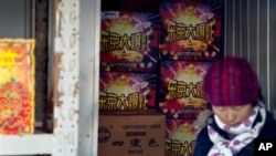"""Seorang penjual keluar dari gudang tempat penyimpanan petasan bermerek """"Tokyo Big Bang"""" di Beijing (6/2). (AP/Andy Wong)"""
