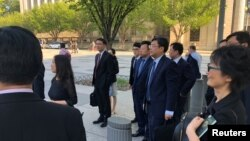 Members of Chinese Commerce Vice Minister Wang Shouwen's delegation wait to be admitted into the U.S. Treasury Department for trade talks with members of the Trump administration in Washington, D.C., Aug. 23. 2018.