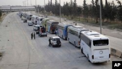 This photo released March, 22, 2018, by the Syrian official news agency SANA, shows Syrian government forces overseeing the evacuation by buses of rebel fighters and their families, at a checkpoint in eastern Ghouta, Syria.