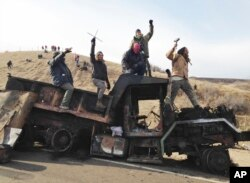 FILE - Protesters against the Dakota Access oil pipeline stand on a burned-out truck near Cannon Ball, N.D., that they removed from a long-closed bridge near their camp in North Dakota, Nov. 21, 2016.