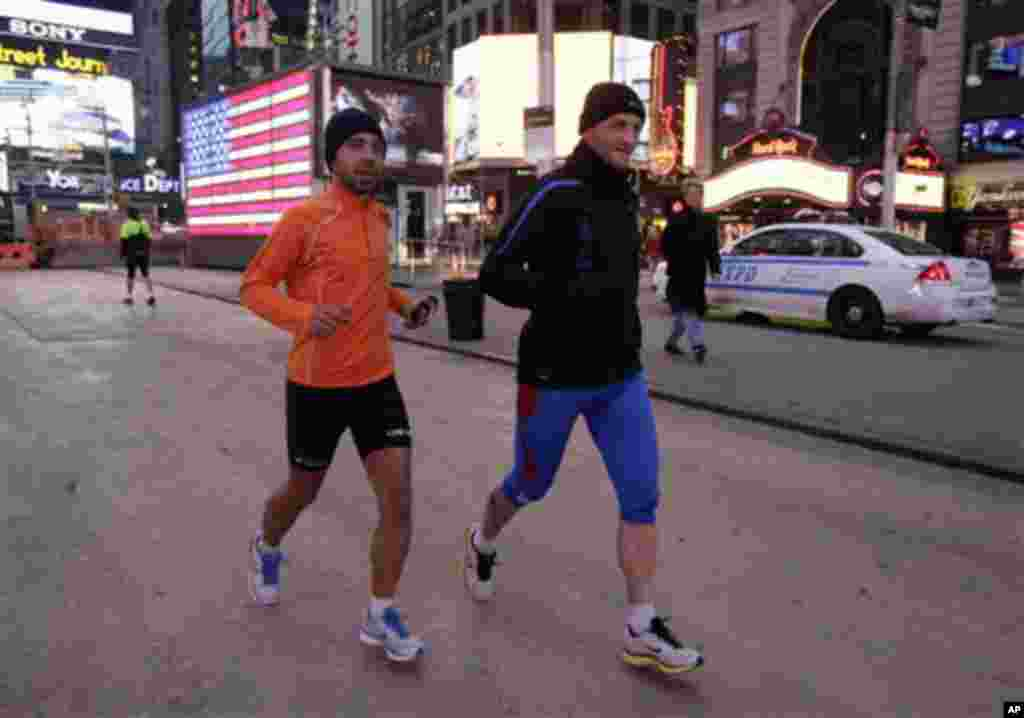 Ricardo Burnia, left, and Simon Capaccioni, from Perugia, Italy, train for Sunday's New York City Marathon in New York's Times Square, Friday, Nov. 2, 2012. (AP Photo/Richard Drew)