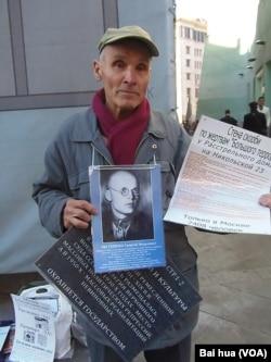 涅斯杰连科手持被处决的父亲照片,以及介绍当年最高军事法庭的资料,他呼吁把最高军事法庭遗址改建成红色恐怖博物馆 (美国之音白桦拍摄)