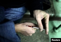 A drug user injects heroin into his hand on a staircase in an apartment block in Moscow, Russia, Nov. 14, 2010.