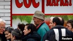 ARHIVA - Ljudi čekaju u redu za hranu ispred prodavnice koju finansijski potpomaže Vlada Srbije, u Beogradu, 31. marta 2009. (Foto: Reuters/Marko Đurica)