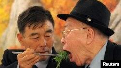 Con trai Ryu Young-il (trái) ở Bắc Triều Tiên gắp đồ ăn cho người cha Ryu Hae-chan ở miền Nam trong một cuộc sum họp gia đình. Hai cha con đã bị ly tán kể từ cuộc Chiến tranh Triều Tiên.