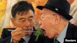 Warga Korea Selatan, Ryu Young-il (kiri) menyuapi ayahnya, warga Korea Utara, Ryu Hae-chan dalam acara makan siang dalam reuni keluarga di Korea Utara. Mereka terpisahkan sejak perang Korea tahun 1950-1953 (Foto: dok). Kedua negara memulai pembicaraan terkait reuni keluarga ini, Jumat (23/8).