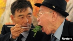 North Korean Ryu Young-il (L) feeds his South Korean father Ryu Hae-chan during their luncheon meeting, in North Korea. They were separated since the 1950-53 war, (File photo).
