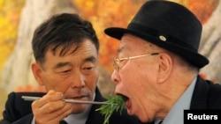 在这张2010年11月4日的资料中,在朝鲜旅游地金刚山举行的南北家人团聚活动中,一位韩国男士为久别的朝鲜父亲喂食。朝鲜目前拒绝恢复南北离散家庭团聚活动。