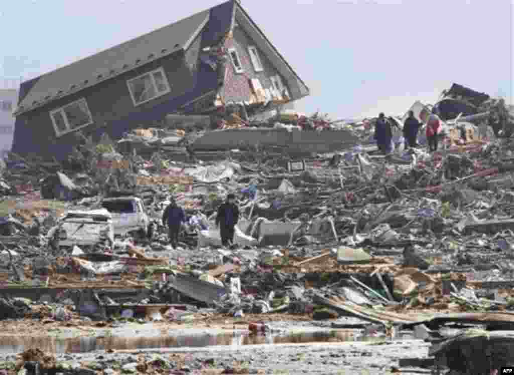 CORRECTS SOURCE - In this March 13, 2011 photo, people look at the upper part of a house washed away by tsunami in Minamisanrikucho in Miyagi Prefecture, two days after a powerful earthquake-triggered tsunami hit the country's northeast coast. (AP Photo/T