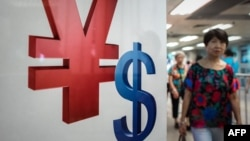 A woman walks past a yuan, left, and a U.S. dollar, right, currency sign in Hong Kong, Aug. 13, 2015.