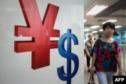 FILE - A woman walks past a yuan (L) and a US dollar (R) currency sign in Hong Kong on August 13, 2015.