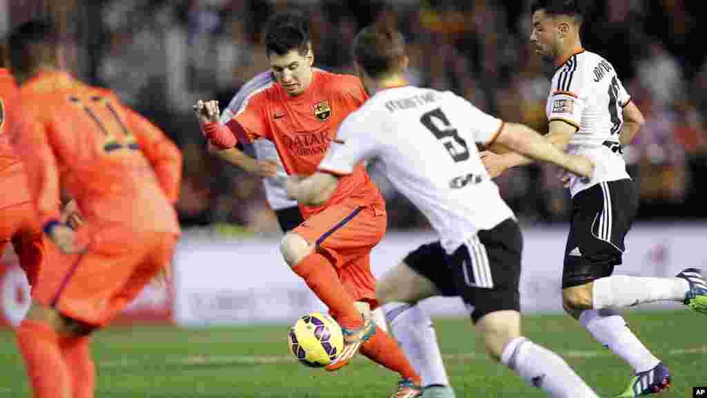 Lionel Messi de Barcelone, de l'Argentine, fonce avec la balle, dépassant Mustafi de Valence au cours d'un match de football de la Liga espagnole au stade Mestalla à Valence, Espagne, 30 novembre 2014.