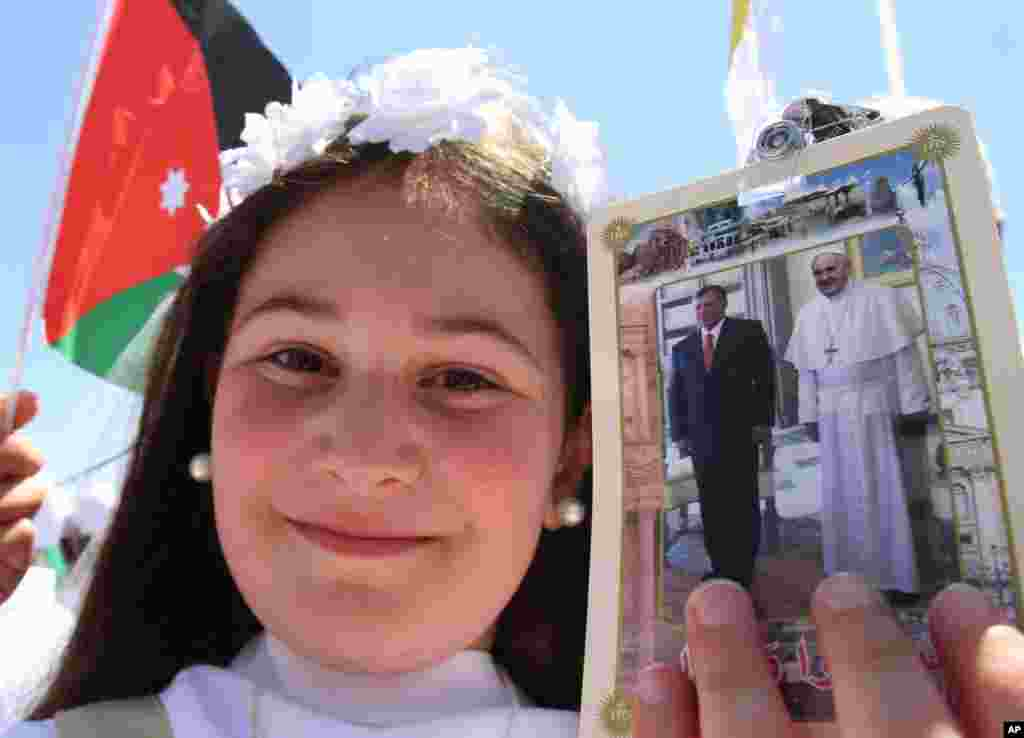 A young girl holds a photo of Pope Francis and Jordan's King Abdullah as people congregate at Amman's International Stadium to wait for the arrival of Pope Francis Amman, May 24, 2014.