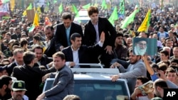 Iranian President Mahmoud Ahmadinejad, center, waves to well wishers from his car, during an annual rally commemorating the anniversary of the 1979 Islamic revolution, which toppled the late pro-U.S. Shah, Tehran, February 10, 2013.