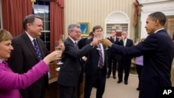 President Barack Obama shares a toast in the Oval Office with the members of his National Security Staff who worked on the New START nuclear arms control agreement, 22 Dec 2010.