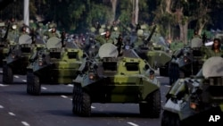 FILE - Cuban military vehicles parade along the Plaza de la Revolucion to mark the 50th anniversary of the failed Bay of Pigs invasion in Havana, April 16, 2011.