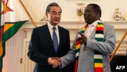 Zimbabwe President Emmerson Mnangagwa (R) and Chinese Foreign Affairs Minister Wang Yi (L) pose during their meeting at State House in Harare on January 13, 2020 as part of Wang Yi's visit to the country. (Photo by Jekesai NJIKIZANA / AFP)