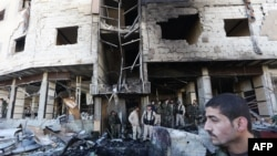 Syrian pro-government forces inspect the damage following suicide bombings in the area of a revered Shiite shrine in the town of Sayyida Zeinab, on the outskirts of the capital Damascus, Jan. 31, 2016.