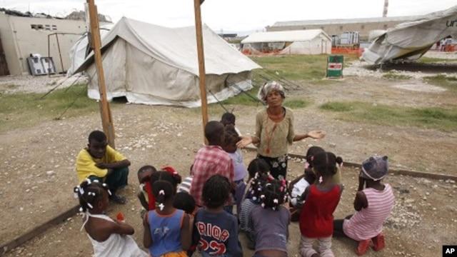 An earthquake survivor prays with children in Port-au-Prince, Haiti (Nov 2010 file photo)
