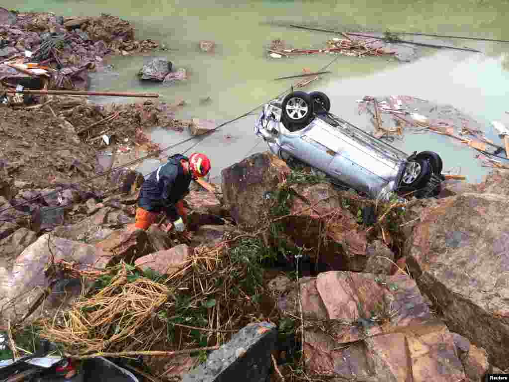 A rescue worker is seen next to an overturned car at the site of a landslide caused by heavy rains brought by Typhoon Megi, in Sucun Village, Lishui, Zhejiang province, China.