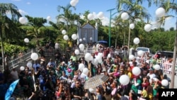 Relatives and supporters of the victims of the infamouse Maguindanao massacre, including Philippine Justice Secretary Leila de Lima (C-partly hidden), release white balloons into the air during the fifth-year anniversary commemoration at the massacre site in Ampatuan, Maguindanao province, on the southern Philippine island of Mindanao, on November 23, 2014. Senior Philippine officials vowed on November 23 to deliver justice as the nation marked the fifth anniversary of the country's worst political massacre that left 58 dead, including 32 journalists. (AFP/Mark Navales)
