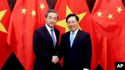 1일 왕이 중국 외교부장이 베트남 하노이에서 팜 빈 민 부총리 겸 외교부 장관을 만나 악수하고 있다.