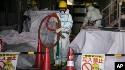In this Feb. 12, 2020, photo, a worker in a hazmat suit carries a hose while working at a water treatment facility at the Fukushima Dai-ichi nuclear power plant in Okuma, Fukushima Prefecture, Japan.